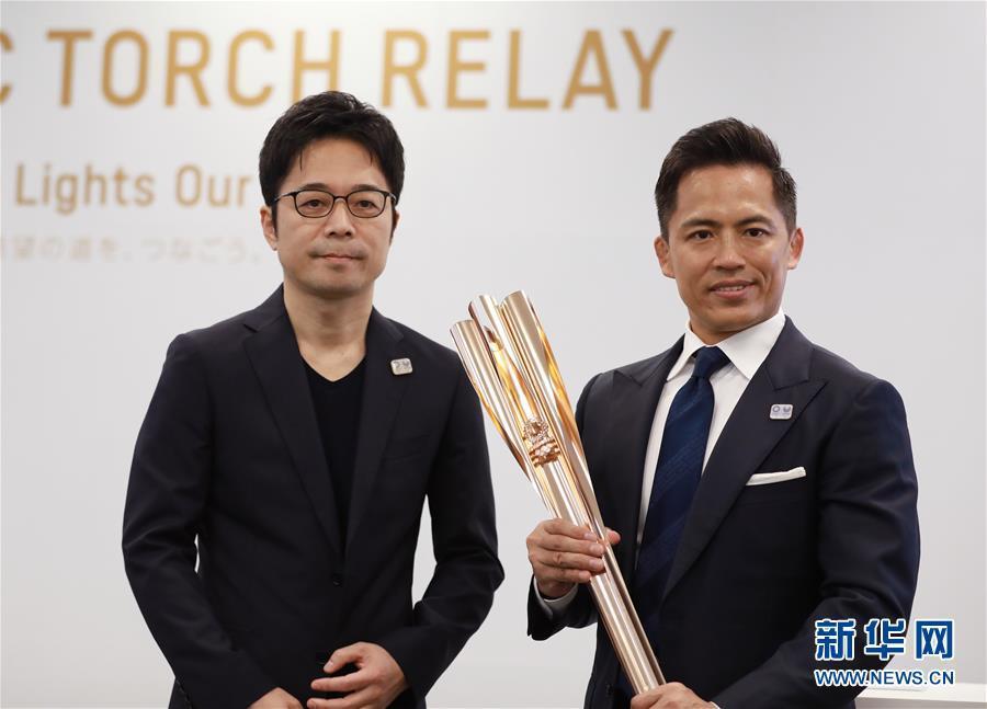 3月20日,东京奥运会圣火传递大使,日本柔道名将野村忠宏(右)与火炬