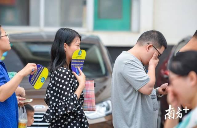 在枯燥的等待下,队伍旁的垃圾站也开始进行垃圾清运,排队的家长和孩童无不皱眉捂鼻,屏住呼吸。 南方日报记者 曾亮超 摄