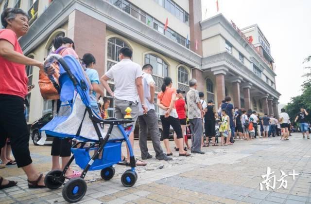 早上七点半,新城计免门诊门口等候接种疫苗的市民已经排队站成了一条近百米长的队伍。 南方日报记者 曾亮超 摄