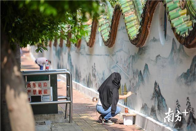 中午的升平街里,在太阳底下画着墙画的市民顶不住高温直晒,用外套遮挡阳光。 南方全媒体记者 曾亮超 摄