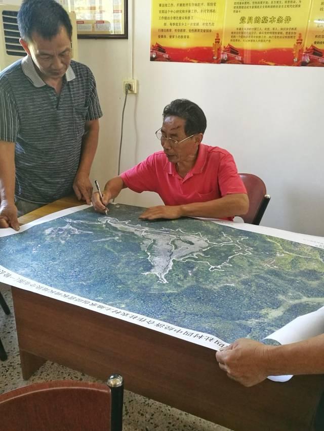 梅县区松口镇四社村原党支部书记刘勉(右一)生前与村民商讨工作。资料图片