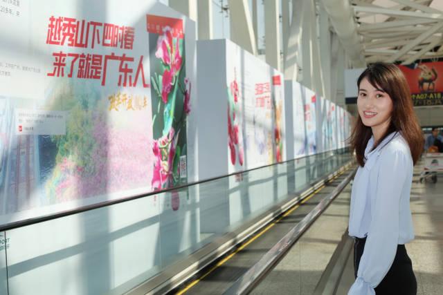 """南方+主播小姐姐佳欣在白云机场""""来了就是广东人""""宣传牌前。"""