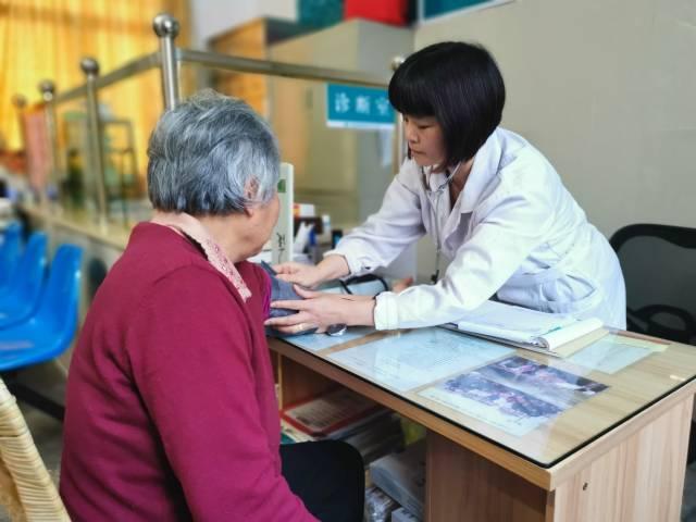 村医黄春容正在为村民量血压?;畦红?摄