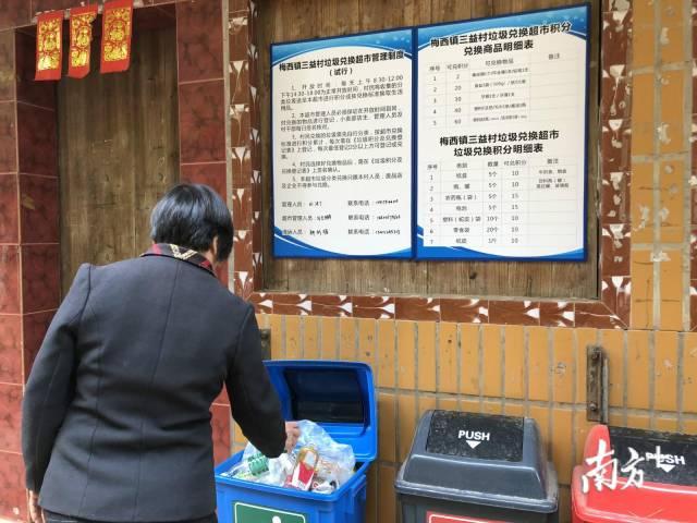 """在梅西镇三益村的""""垃圾兑换超市""""内,村民将收集好的垃圾放进垃圾桶。何苑妮 摄"""