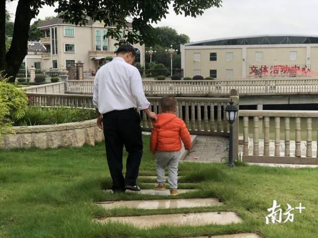 村民带着孩子在幸福公园里散步。何苑妮 摄