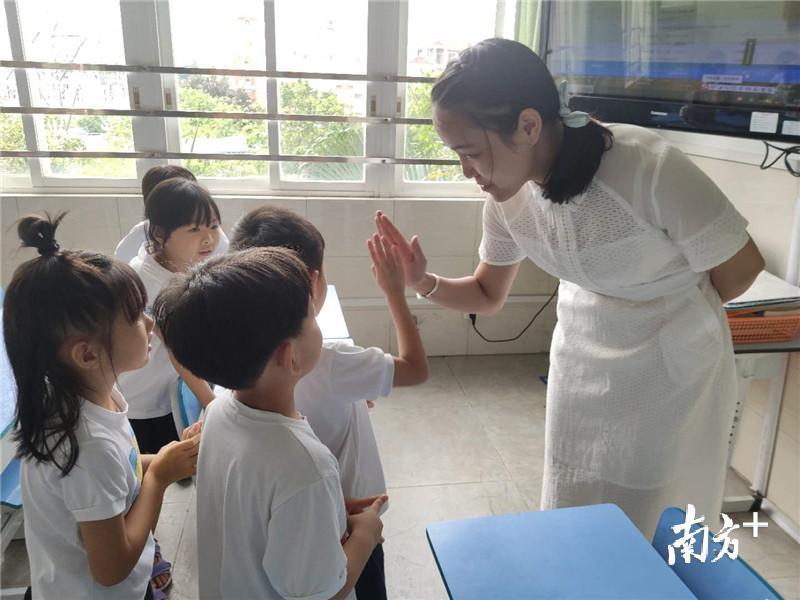 在课堂游戏中,李老师与答对问题的学生一一击掌。