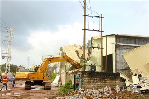 5日,在五沙社区沙坑工业区内,钩机和洒水车联合作业拆除违建。