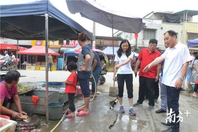 """在水头镇农贸市场, 督导检查组发现,商贩当街""""宰鱼""""造成污水横流,影响市场环境卫生。程浩 摄"""