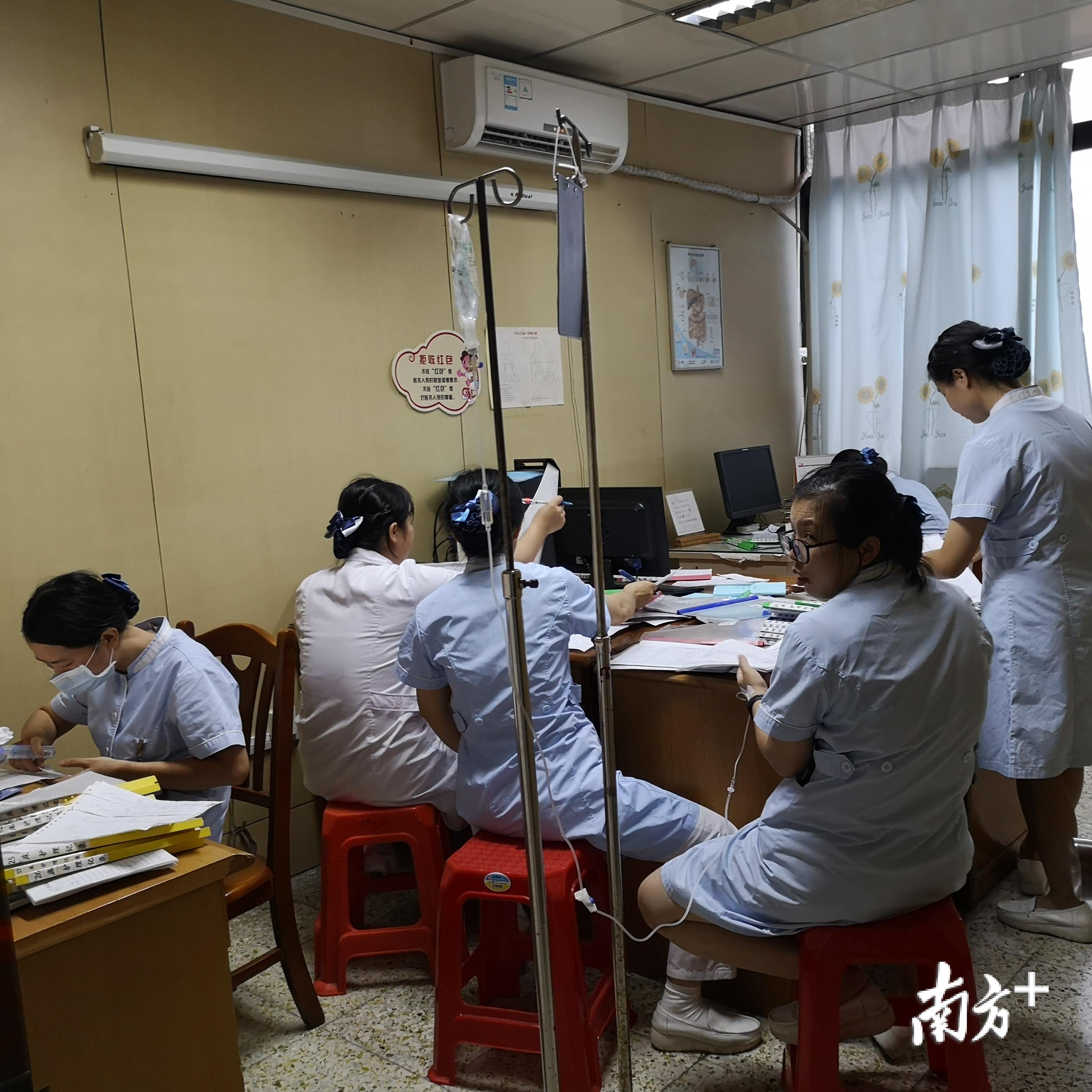 内二科护士廖秀雯左手打着点滴,右手则在书写着护理记录,此前她已连轴工作了12个小时。通讯员供图