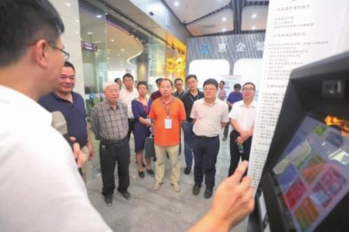 专家组在区行政服务中心智慧新城大厅参观,了解市民之窗的办事流程。珠江时报记者/穆纪武摄