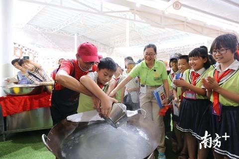 在活動現場,來自高明區富灣小學的學生們,跟著師傅一起學習瀨粉的制作工藝。