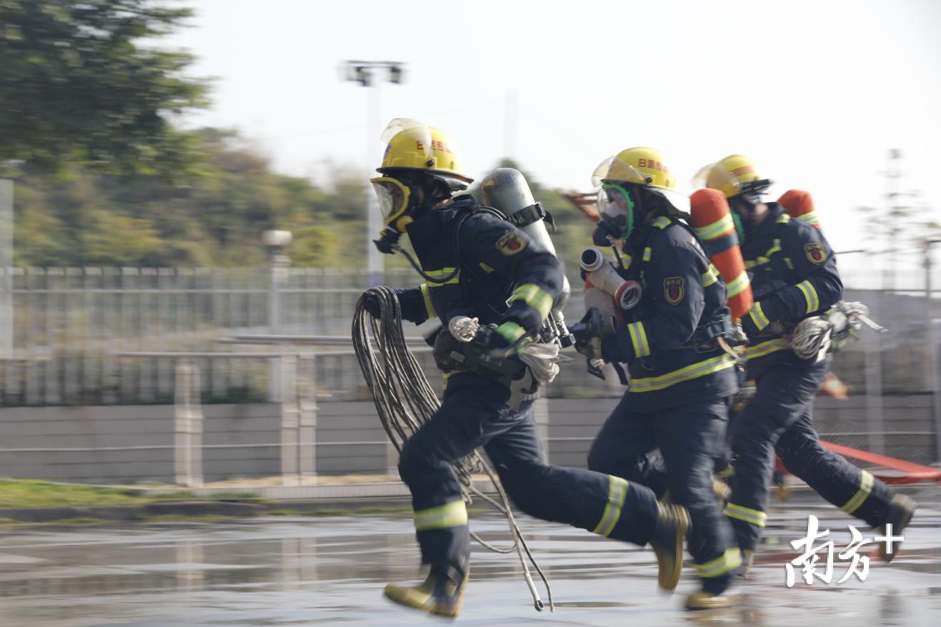 专职消防队员参与携带灭火器材飞奔二楼灭火比赛。曾润生 摄