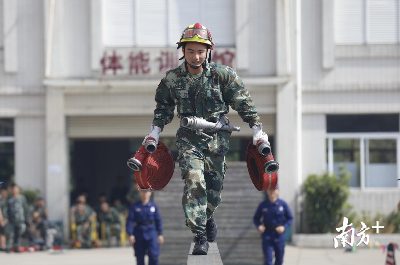 专职消防队员携带水带奔跑独木桥。曾润生 摄
