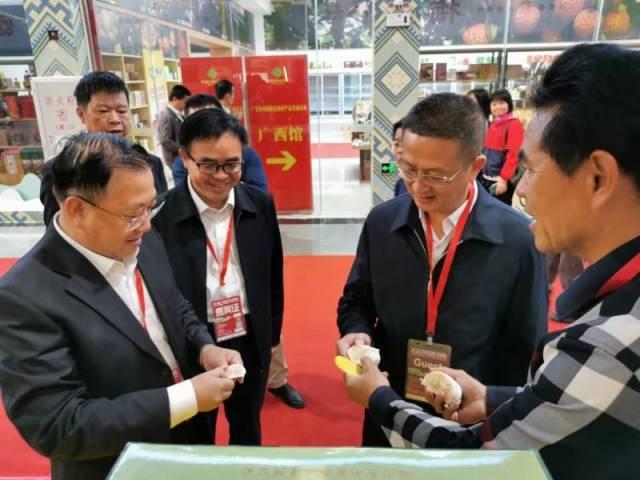 梅州市农业农村局党组成员、副局长陈爱东(右二)为广东省农业农村厅副厅长高庆营(左一)介绍梅州柚
