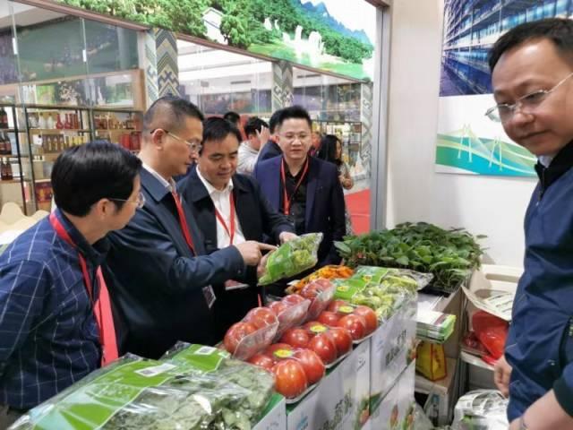 梅州市人民政府副秘书长梁志坚(左三)在梅州名特优新农产品展位前参观