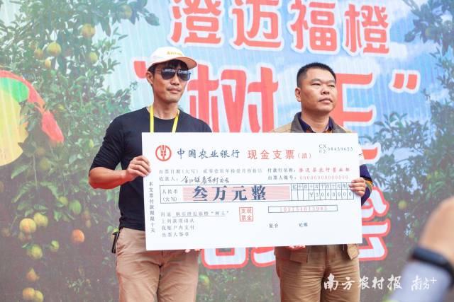 """福橙""""树王""""拍出3万元高价,资金捐赠给金江镇贫困村春芳村,由该村村支部书记徐日兰(右)领取。"""