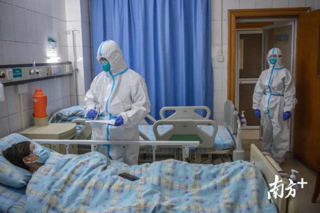 医生在隔离病房内询问被新型冠状病毒感染的肺炎患者。南方日报记者张梓望李细华摄