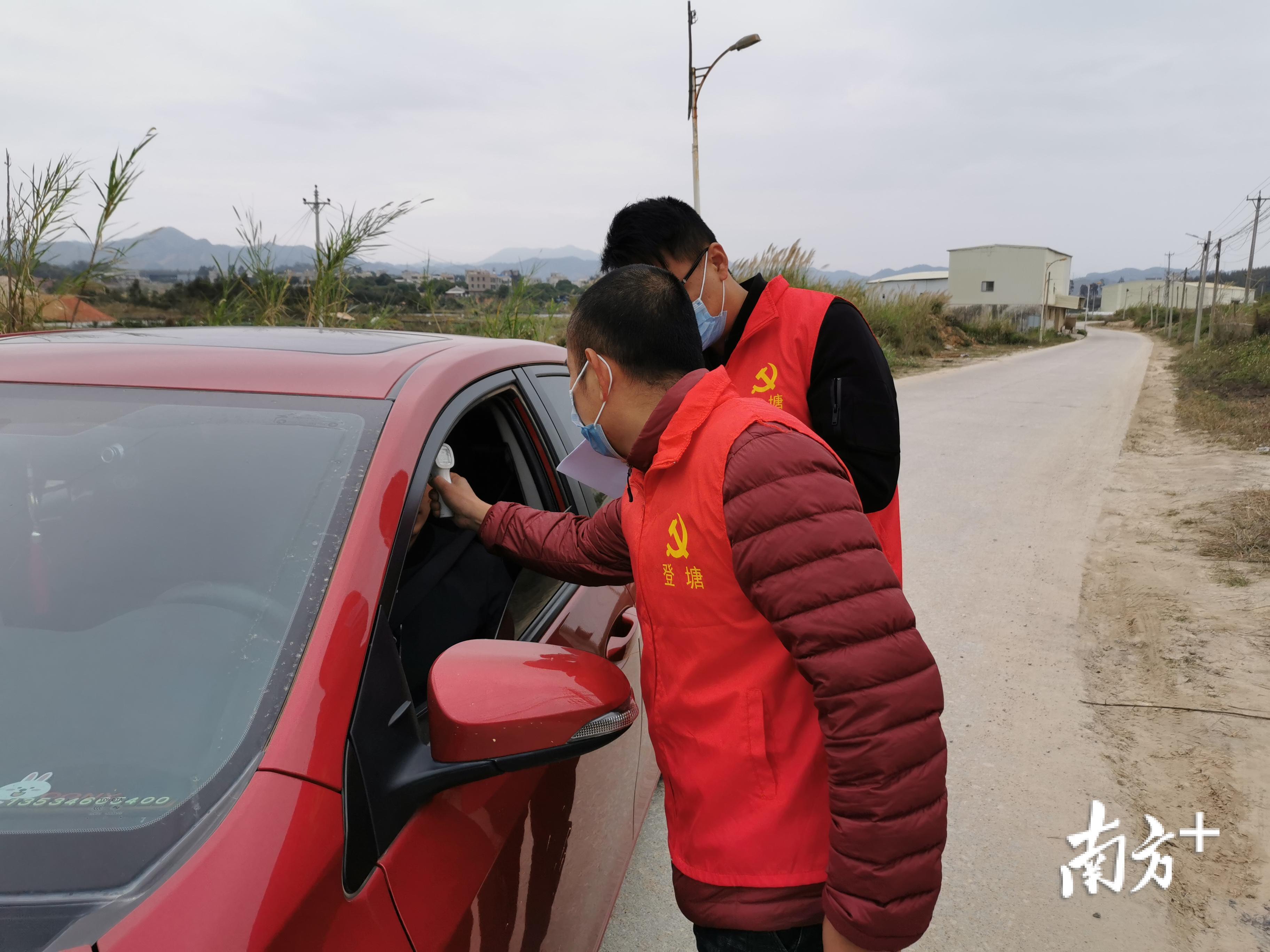 登塘镇党员志愿队在为进村人员测体温