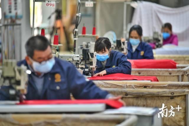 佛山西樵黛富妮家纺复工复产,缝制车间内员工戴着口罩进行生产。戴嘉信 摄