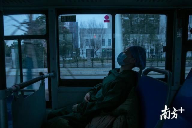 2月24日晚,开往武汉客厅方舱医院的路上,窗外行人稀少,晕车的她上车后闭目养神。南方日报记者 吴明 罗斌豪 摄