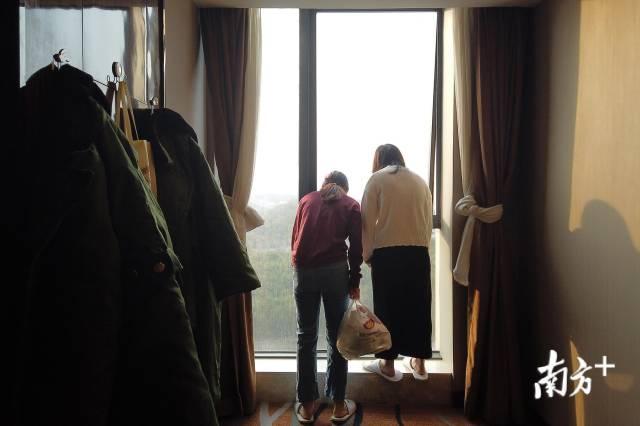 2月23日,武汉天气转晴,刘家怡和同事出门打饭经过窗边停下脚步。