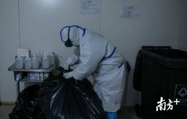 2月24日晚,废弃的防护服堆满垃圾桶,刘家怡将它整理打包。南方日报记者 吴明 罗斌豪 摄