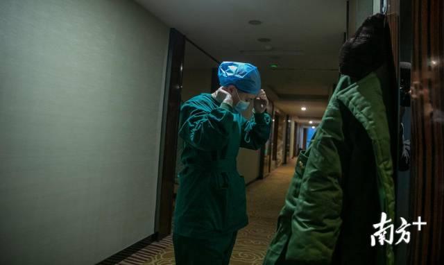 2月24日,出门前,刘家怡在酒店走廊换上干净的口罩。