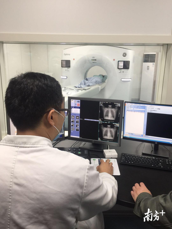 """病人自行躺床后,""""深度天眼""""便自动定位扫描部位的中心位置,医护人员在操作间内便能迅速完成CT扫描操作。夏小荔 摄"""