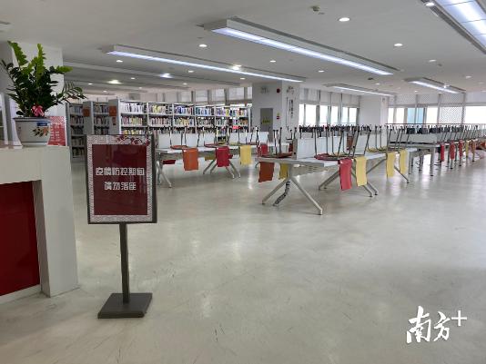 """三楼图书借阅区看到,在区域显眼处皆放置了""""疫情防控期间请勿落座""""提示牌。"""