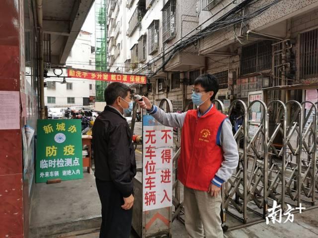梅县区党员志愿者为进入小区的市民测量体温。受访者供图