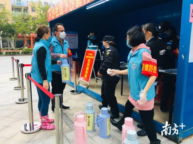 """位于深圳市大鹏新区的一个小区内,志愿者们正在为抗疫一线工作人员送上""""暖心凉茶""""。受访者供图"""