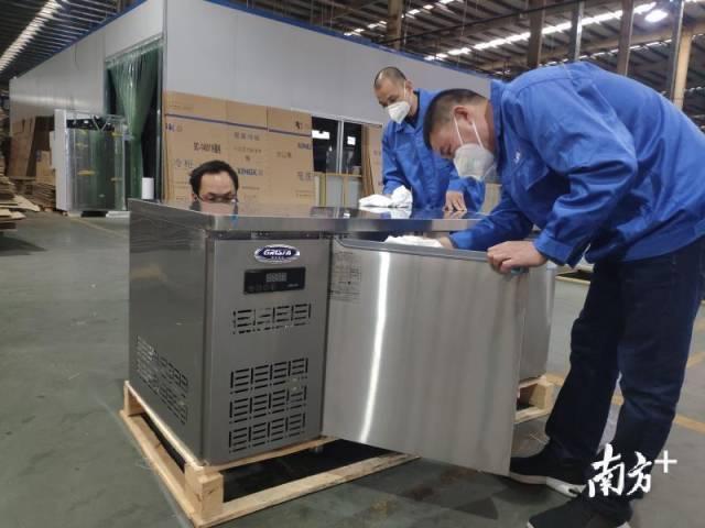 工作人员在检查发往武汉的厨柜冰箱。
