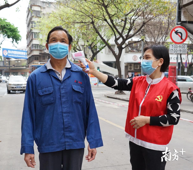 莫悦明(右)为进入社区的人员测温。李嘉欣 摄