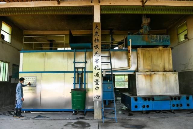 在大东镇坪山村的垃圾无害化减量中心,工人将垃圾送进处理机送料口后,对垃圾进行高温分解,实现垃圾就近处理,减少了二次污染。(南方日报记者 何森垚 摄)