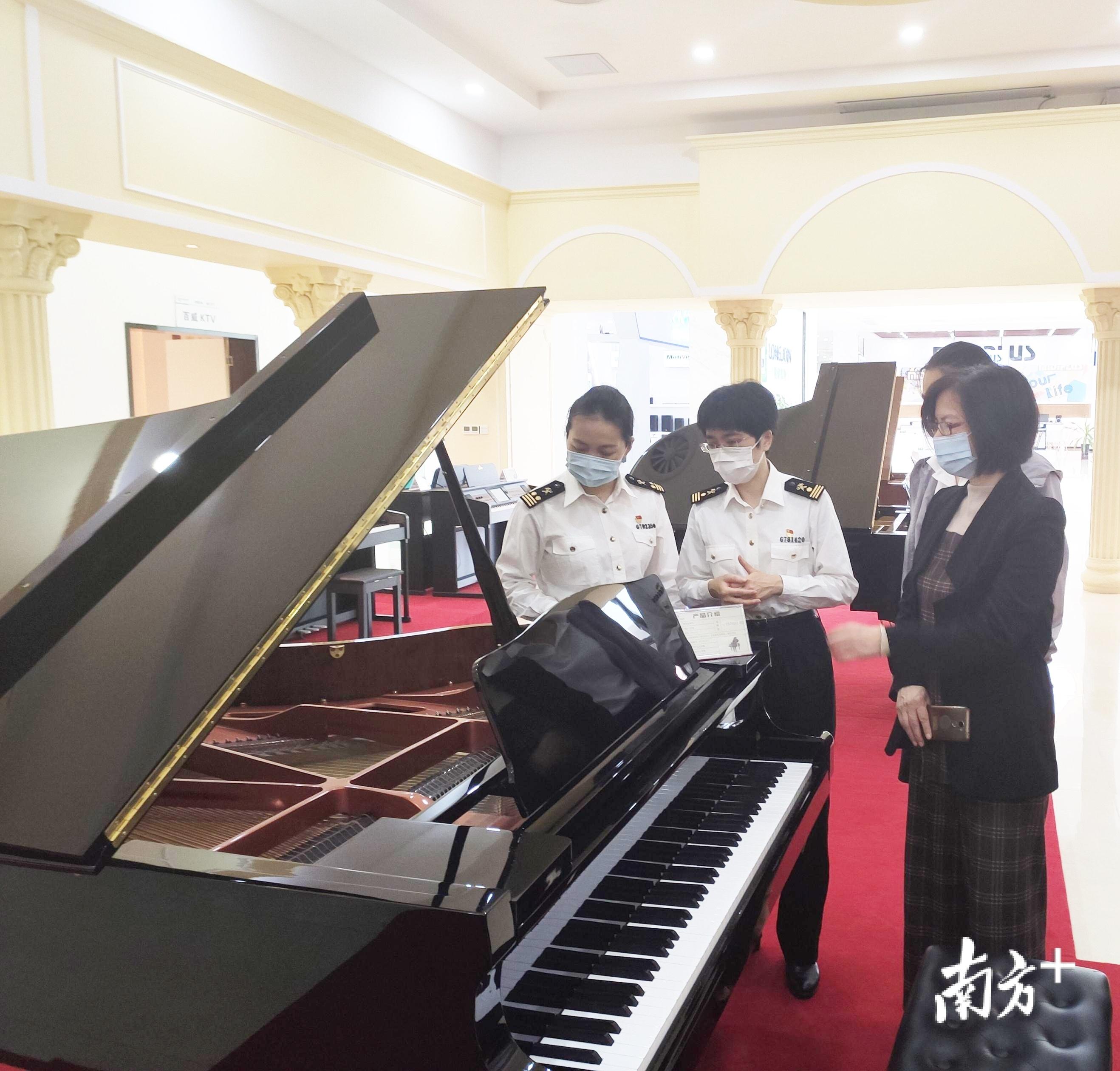 湛江海关所属霞海海关关员查看三角钢琴成品。