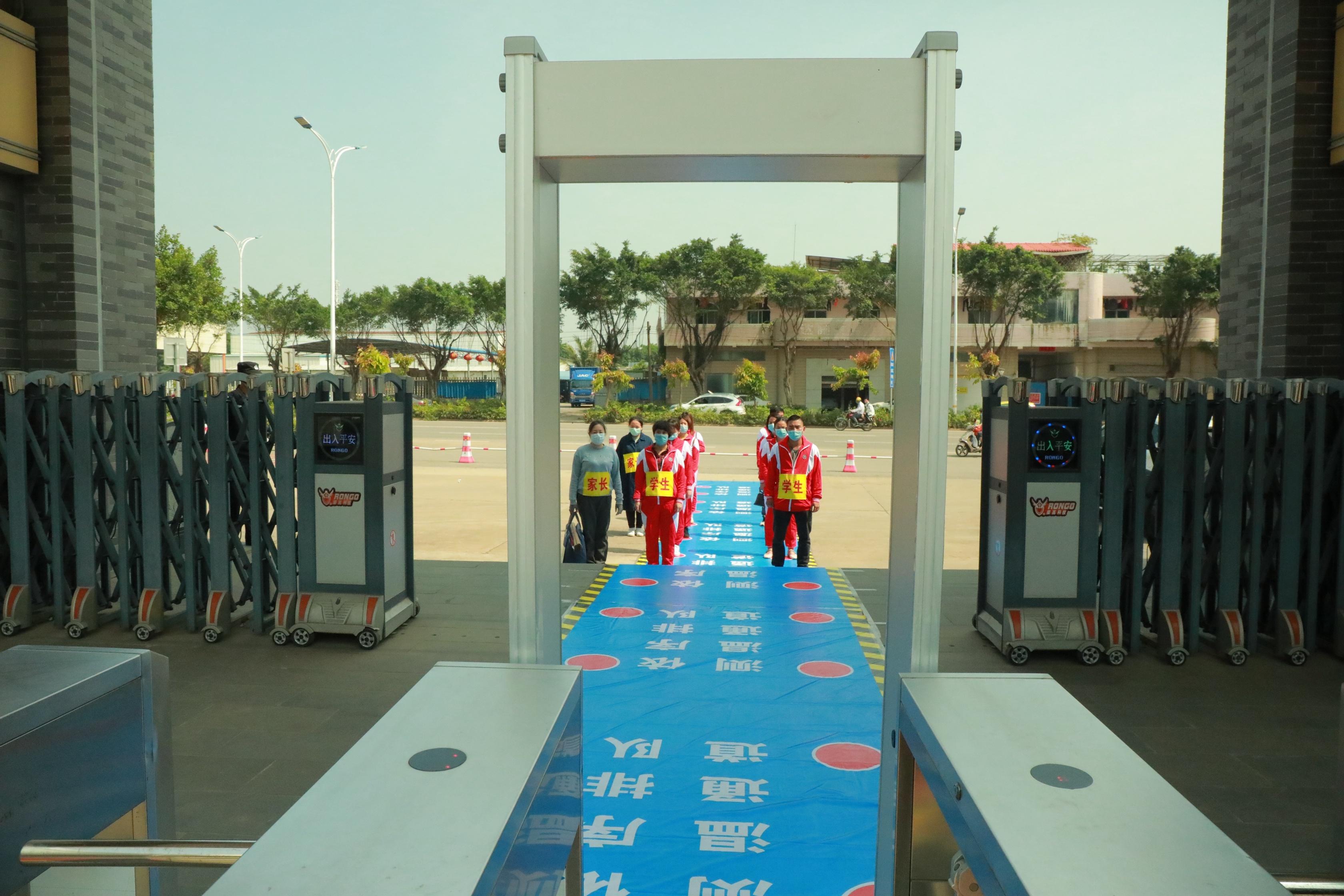 4月15日,湛江市北大附属实验学校开展应急演练,师生间隔1米有序通过红外线测温仪进入校园