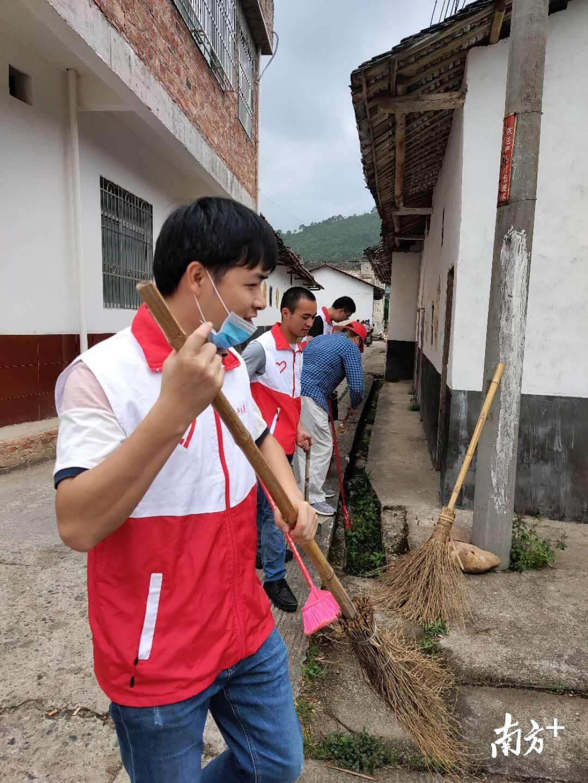 志愿服务队清扫横岭村里的沟渠垃圾。