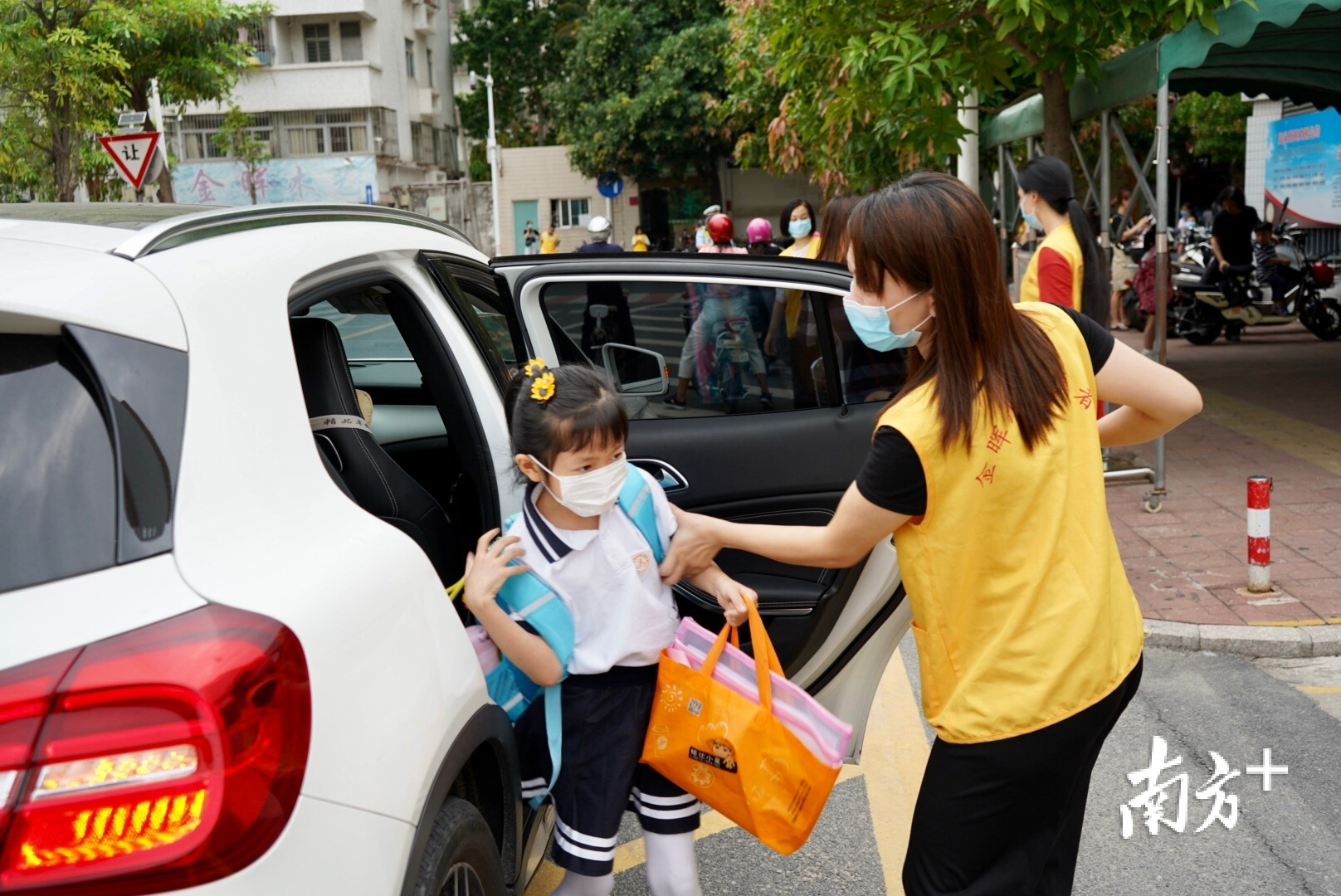 家长志愿者在学校门口协助维持秩序。杨立轩摄