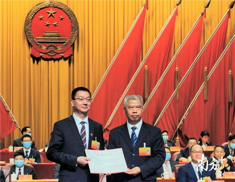 谭星海(左一)获颁当选证书。