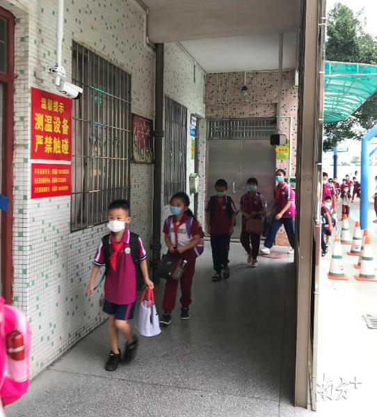 蔡边小学的学生经过热成像系统进行二次测温。