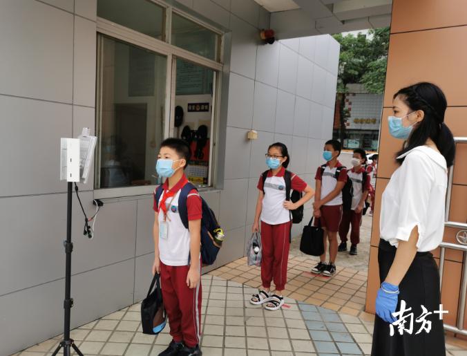 同学们戴着口罩、背着书包、穿着整洁的校服,有序排队,接受体温检测后,精神抖擞地进入久违的校园。