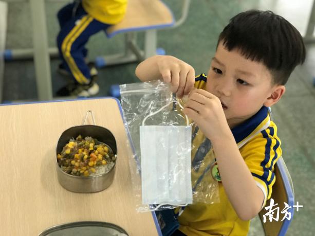 小学生返学后,在老师的指引下,将口罩装起再用餐。 校方供图