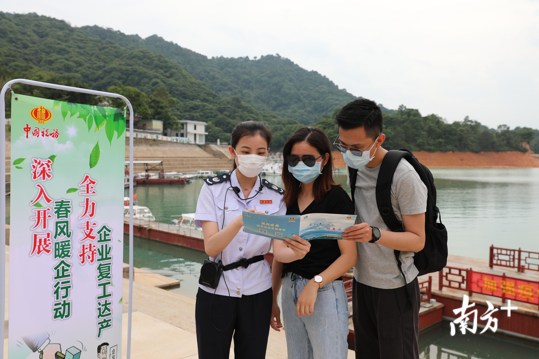 东源县税务人员在万绿湖景区向游客介绍《景区旅游指南·税费优惠政策指引》。邱依新 摄
