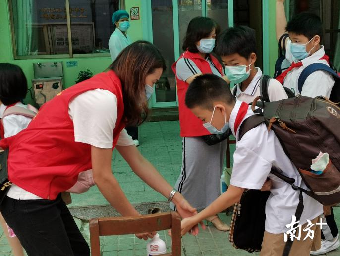 云东海下东鲁小学的家委指导孩子们洗手,做好防疫措施。