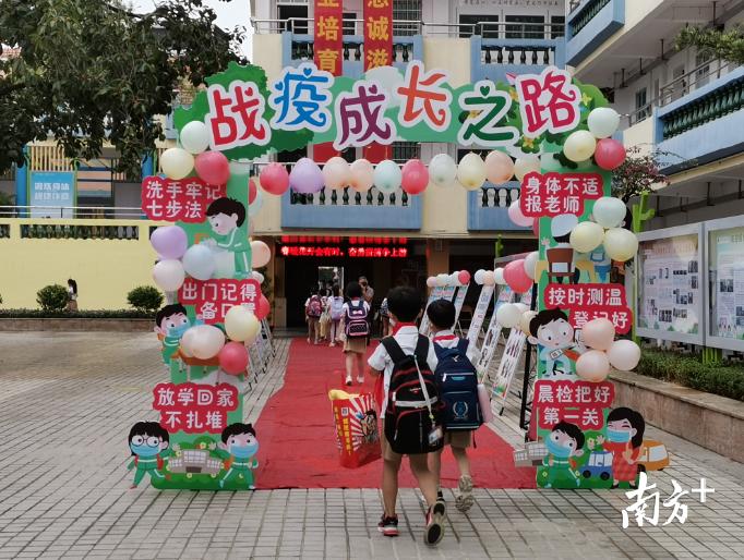 """云东海下东鲁小学的学生们正通过学校特意准备的""""战疫成长之路""""进入课室。"""