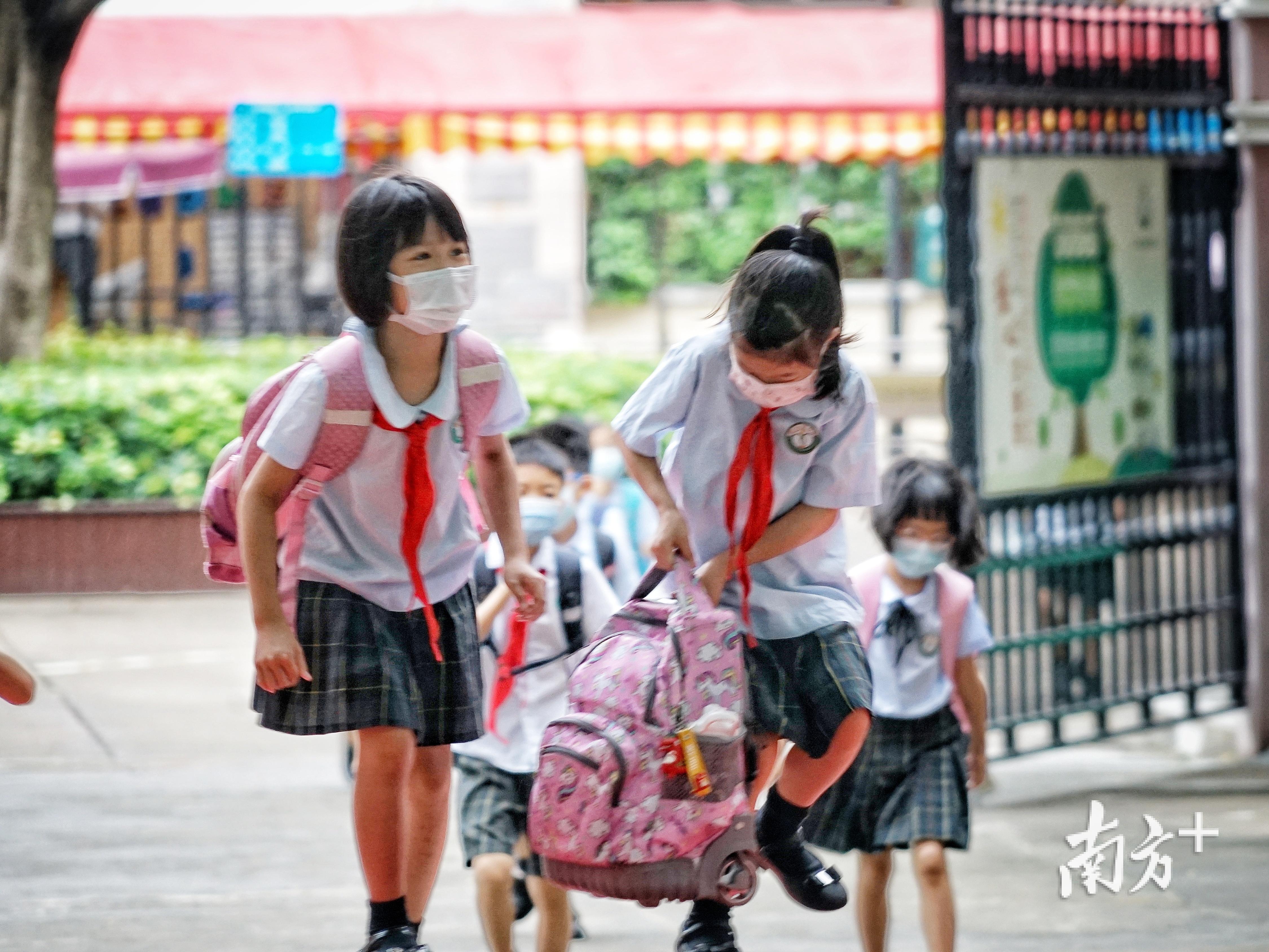 返校的小学生,拎着装有书本的背包。