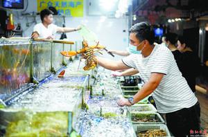 永新海鲜农贸市场,商贩将顾客挑选的海鲜捞起,准备交易。宋福亮 摄