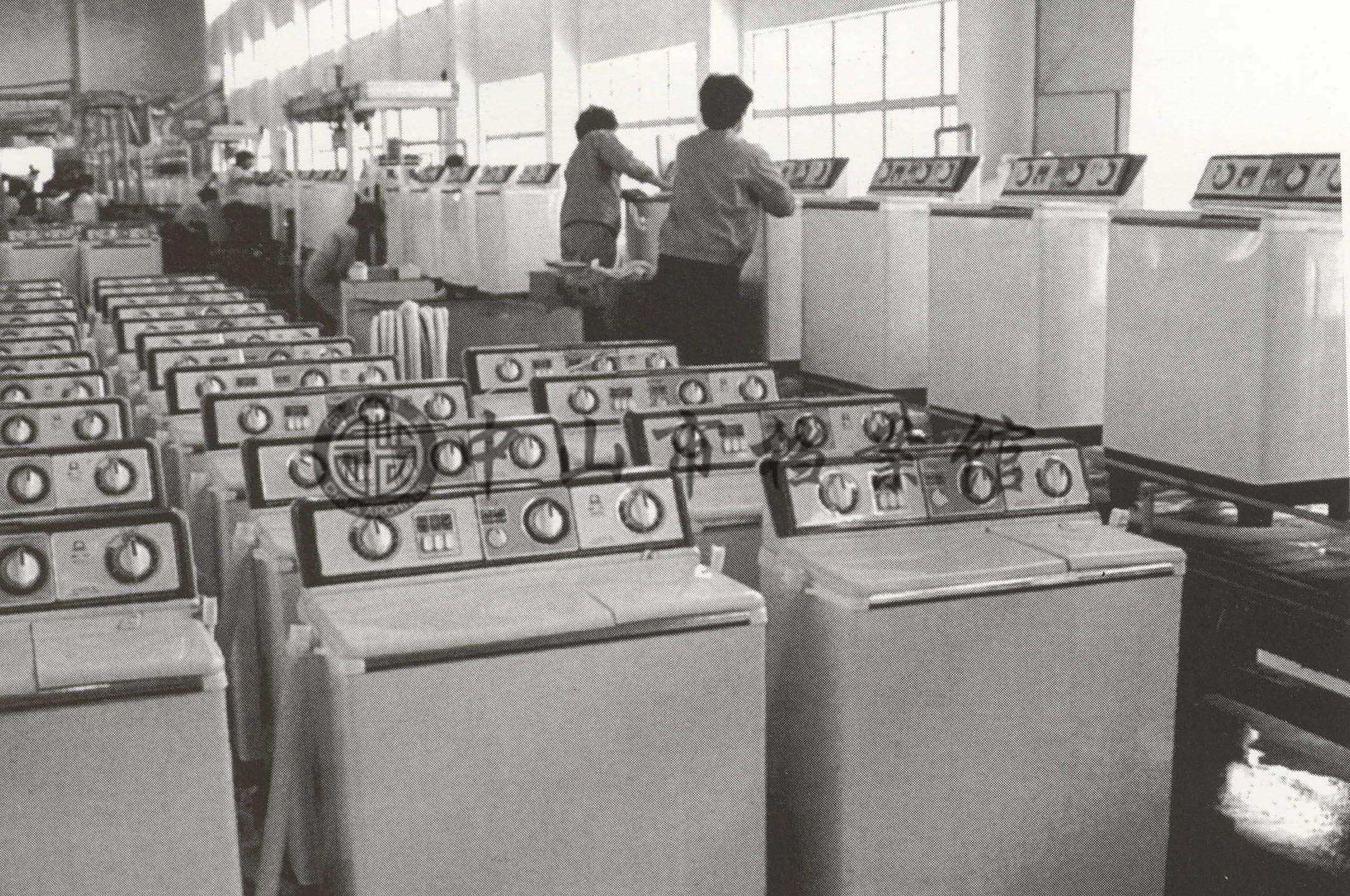 """中山洗衣机厂引进外国先进设备,年产30万台的""""威力牌""""双桶洗衣机。"""