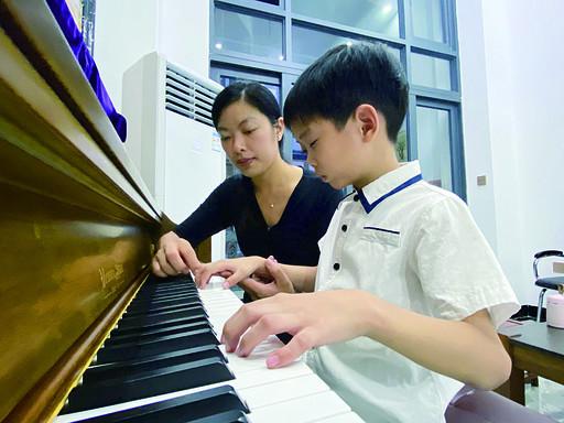 小谭在李晓明的指导下专心练琴。 西江日报记者 赖小琴 摄