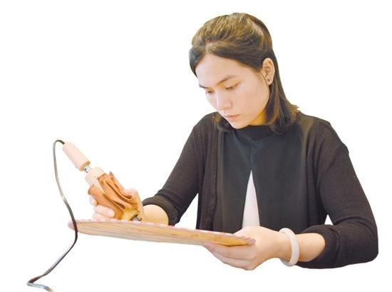余惠云在烙火画扇。